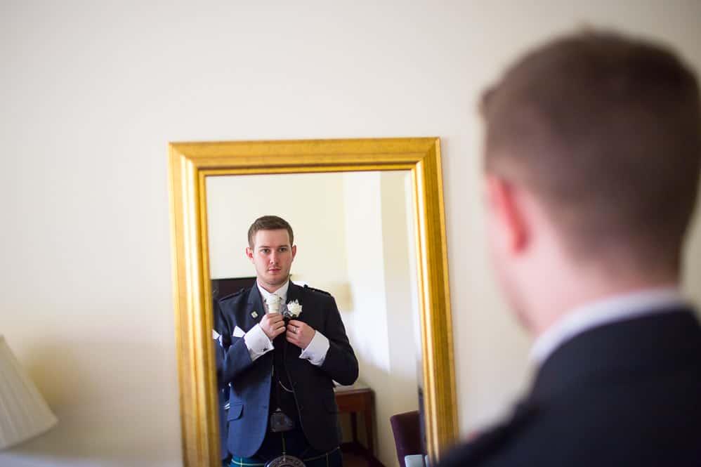 1 groom looks in the mirror