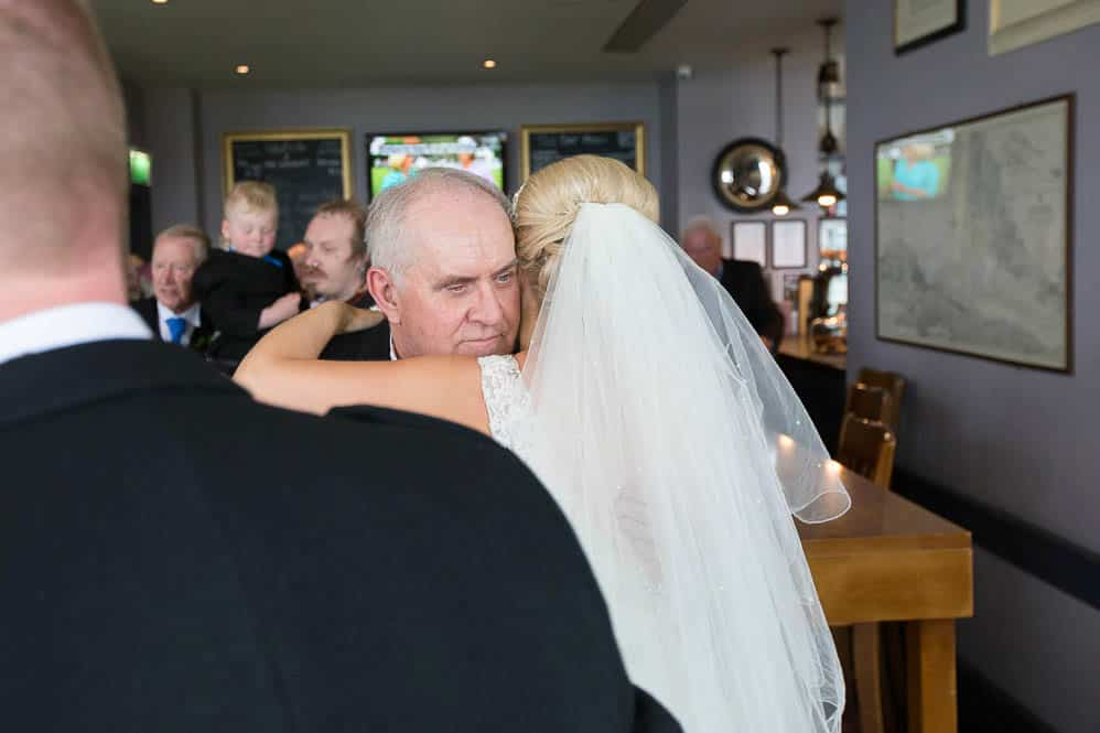 16 bride and father hugging
