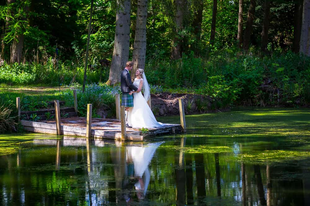 Fernie Castle wedding bride and groom at pier lake reflection in water