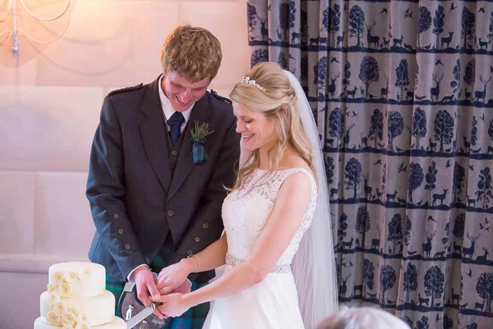 Fernie Castle wedding cutting wedding cake